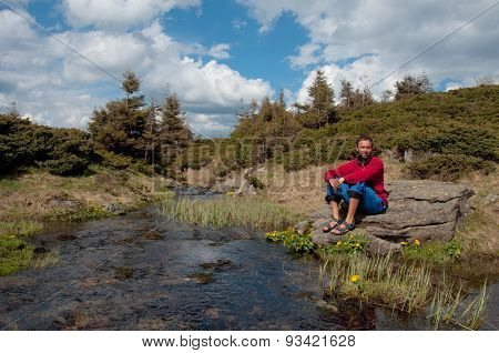 Tourists Sitting On Bank Of Beautiful River In The Forest