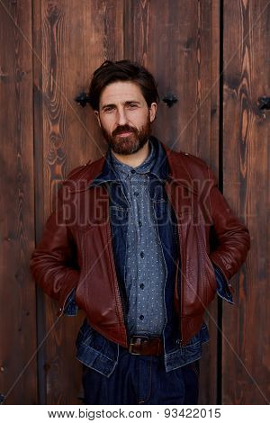 Portrait of a stylish model man with a beard who poses for the camera on the background wall