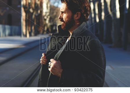 Portrait of mature man in coat standing outside at sunny evening elegant fashion model