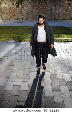 Portrait of a stylish young hipster with black hair and beard who walks through the streets.