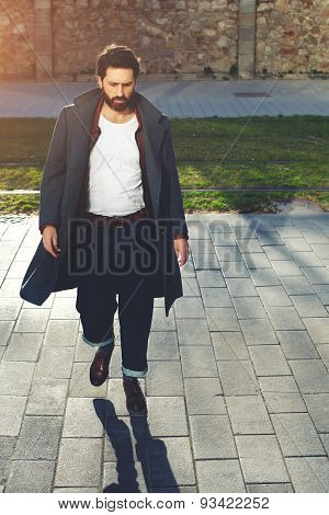 Young stylish man with black hair and beard walking down the street in stylish clothes