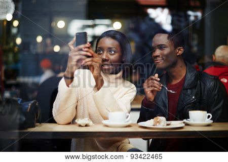 Two dark skinned friends having breakfast in cafe a woman takes photos on your smartphon.