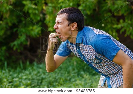 Man on the street nausea vomiting on a green background leaves s