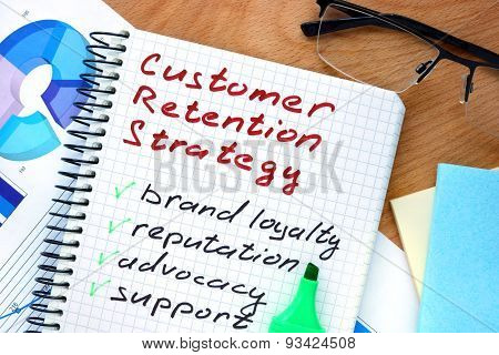 Notepad with words customer retention strategies.