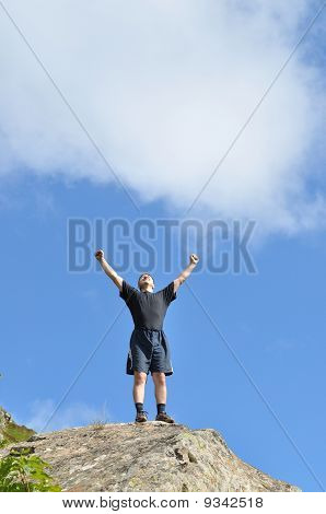 A young man stands on a cliff top and raised his hands to the top expresses delight