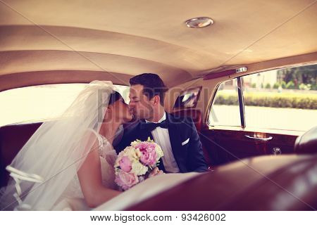 Bride And Groom Kissing In A Retro Car