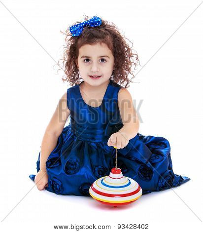 Little girl spinning dreidel sitting on the floor