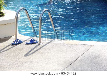 Sandal Near The Swimming Pool Ladder