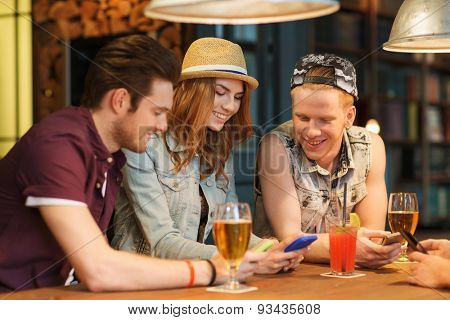 people, leisure, friendship and communication concept - group of happy smiling friends with smartphones and drinks at bar or pub