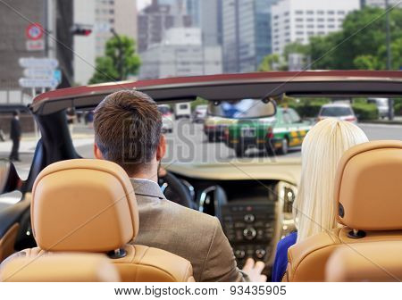 drive, auto transport and people concept - close up of couple driving in cabriolet car from back over city street background