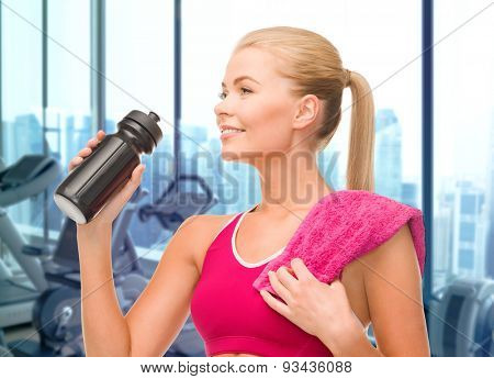 people, sport, fitness and recreation concept - happy woman drinking water from bottle with towel over gym machines background
