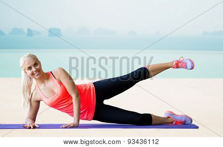 fitness, sport, exercising and people concept - smiling woman raising leg on mat over sea and pool at hotel resort background