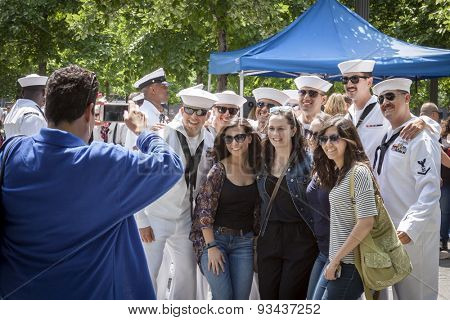 NEW YORK - MAY 22 2015: Group of young women pose with US Navy sailors gathering at the military re-enlistment and promotion ceremony at the National September 11 Memorial site during Fleet Week 2015.