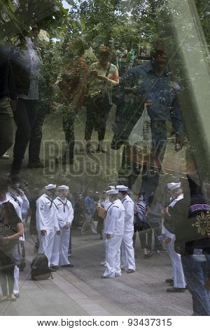 NEW YORK - MAY 22 2015: Reflections of US Navy sailors in the glass of the the National September 11 Museum as they gather for the military re-enlistment and promotion ceremony during Fleet Week 2015.