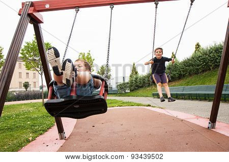 Two Children Playing In The Swing