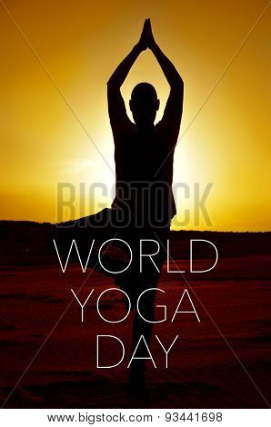 a young yogi man practicing the tree pose outdoors in backlight at sunset and the text world yoga day