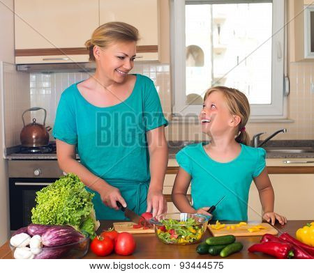 Smiling mother and funny playful daughter cooking together, help children to parents.