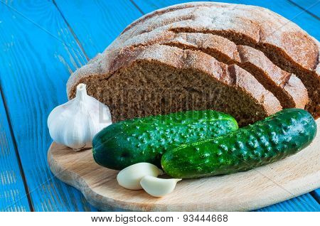 Freshly Baked Bread, Cucumber And Garlic In Rural Or Rustic Kitchen On Vintage Wood Table From Above