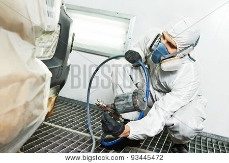 automobile repairman painter painting car body bumper in chamber