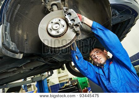 car mechanic examining car wheel brake disc and shoes of lifted automobile at repair service station