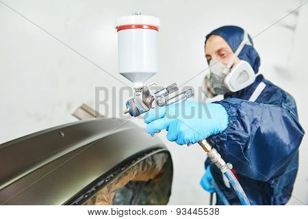 worker  painting auto car bumper in a paint chamber during repair work