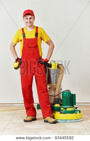Portrait of happy carpenter worker with polishing wood parquet floor grinding machine