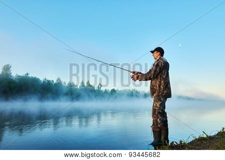 Fisher man fishing with spinning rod on a river bank at misty foggy sunrise
