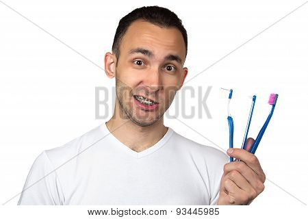 Image of smiling man with brackets and toothbrush