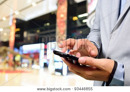 Business Man Using Mobile Phone In Modern Movie Theatre Complex