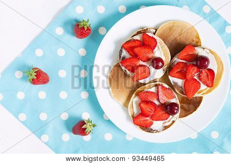 Delicious pancakes traditional sweet dessert on white dish with strawberry and butter. Provence styl