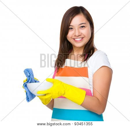 Asian housewife washing dishes with rag