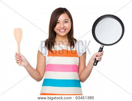 Housewife holding up with frying pan and wooden ladle