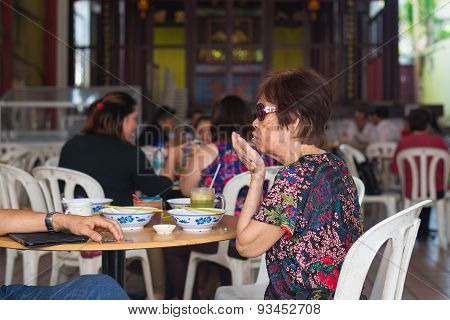Mature Chinese Woman Dining In Food Stall