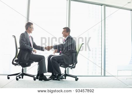 Full-length side view of businessmen shaking hands while sitting on office chairs by window