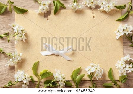 beautiful flowers cherry on branches with a bow and a piece of textured paper on a wooden background texture.