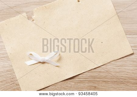 sheet of paper with white bow on a wooden background