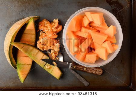High angle shot of a bowl full of cantaloupe pieces next to the rinds and seeds. A knife and spoon are also on the metal kitchen surface.