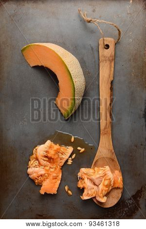 High angle shot of a cantaloupe slice next to a wooden spoon and the seed pulp. Overhead view in vertical format.