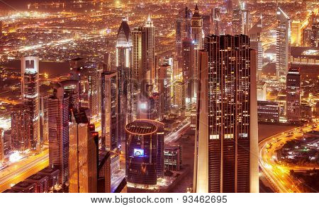 Dubai city at night, beautiful modern buildings glowing lights, bird eye view on gorgeous cityscape, famous business and travel destination, United Arab Emirates