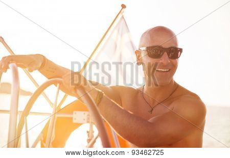 Portrait of handsome shirtless sailor behind helm of sailboat in bright sunny day, enjoying active summer holidays, happy traveling along sea