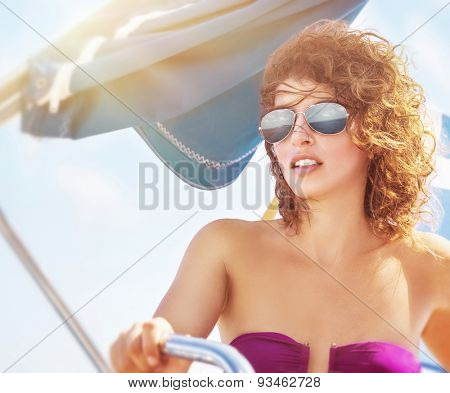 Portrait of a woman driving sailboat, female wearing stylish sunglasses and swimsuit posing at the helm, enjoying summer vacation