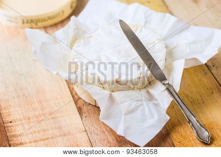 Camembert Cheese Wrapped In Paper With Vintage Knife On Wooden Table