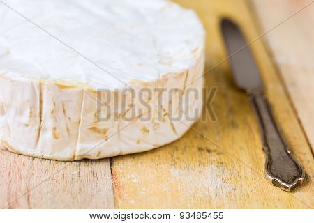 Camembert Cheese And Vintage Knife On Wooden Table