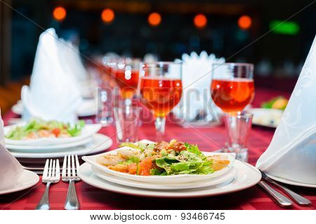 Served banquet table with glasses and salads.