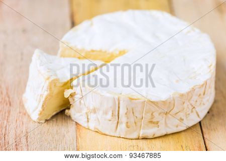 Camembert Cheese With Cut Wedge And Vintage Knife On Wooden Table