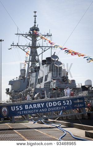 STATEN ISLAND, NY - MAY 24 2015: Two female sailors leave the USS Barry (DDG 52) via the metal gangplank with the ships banner hanging from it while moored at Sullivans Pier during Fleet Week NY 2015.