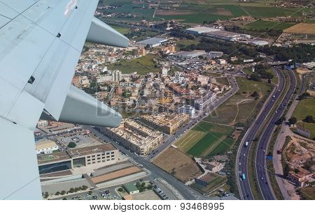 Airplane wing and aerial view with road network east of Palma
