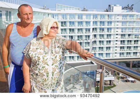 Portrait of elderly man in striped vest with wife on the balcony