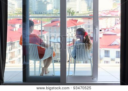 Mother in an orange dress and daughter sitting on the terrace in the room, view through glass