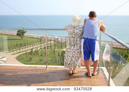 Elderly man in striped vest with wife standing on the balcony